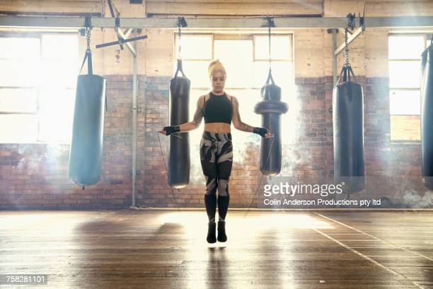 caucasian woman jumping rope in gymnasium near punching bags - boxing sport stock pictures, royalty-free photos & images