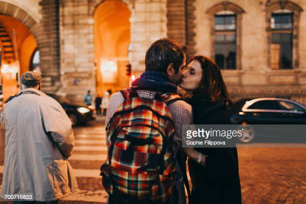 Caucasian woman kissing man on cheek in city at night