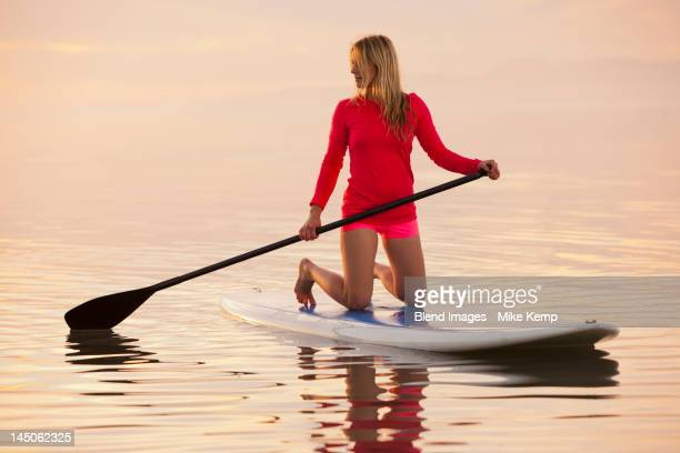 Caucasian woman kneeling on paddle board