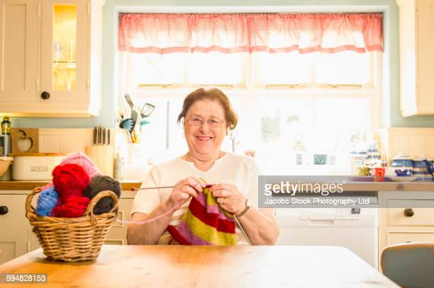 Caucasian woman knitting in kitchen