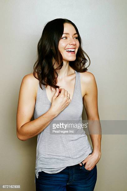 Caucasian woman laughing near wall