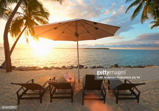 Caucasian woman laying in deck chair on tropical beach