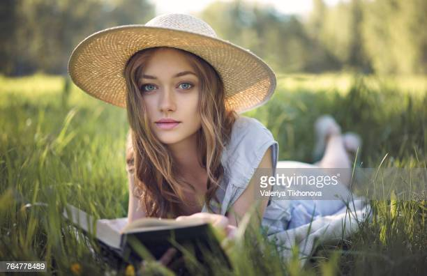 Caucasian woman laying in grass reading book
