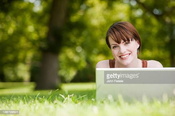 Caucasian woman laying in grass using laptop