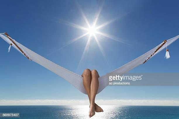 Caucasian woman laying in hammock near ocean under blue sky