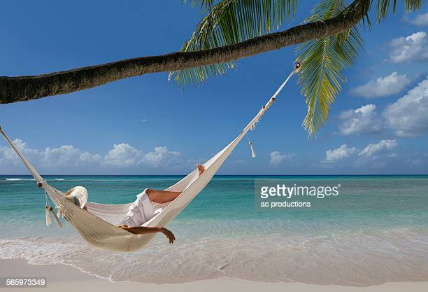 Caucasian woman laying in hammock under palm tree on tropical beach