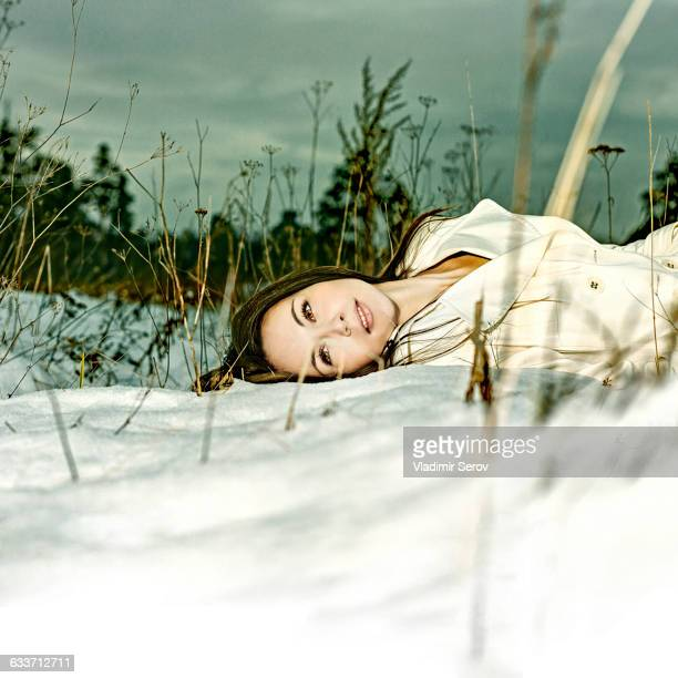 Caucasian woman laying in snow