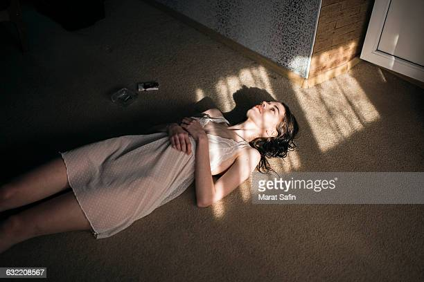 caucasian woman laying in sun spot on floor - drug abuse stock pictures, royalty-free photos & images