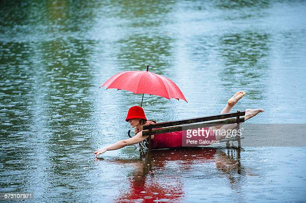 caucasian woman laying on bench in flood - pluie humour photos et images de collection