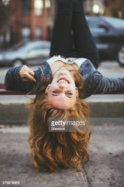 Caucasian woman laying on city sidewalk