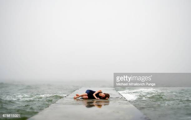 Caucasian woman laying on dock in ocean waves