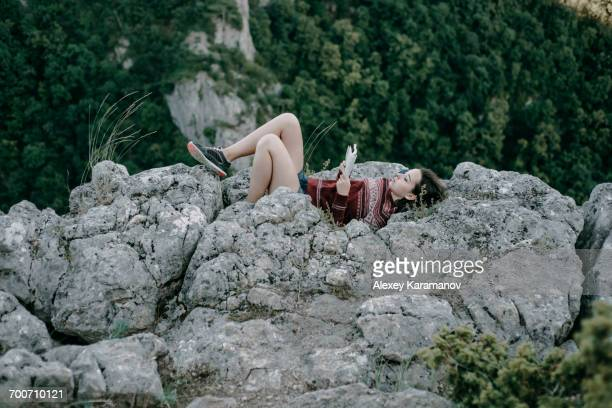 caucasian woman laying on mountain rocks reading magazine - nature magazine stock pictures, royalty-free photos & images