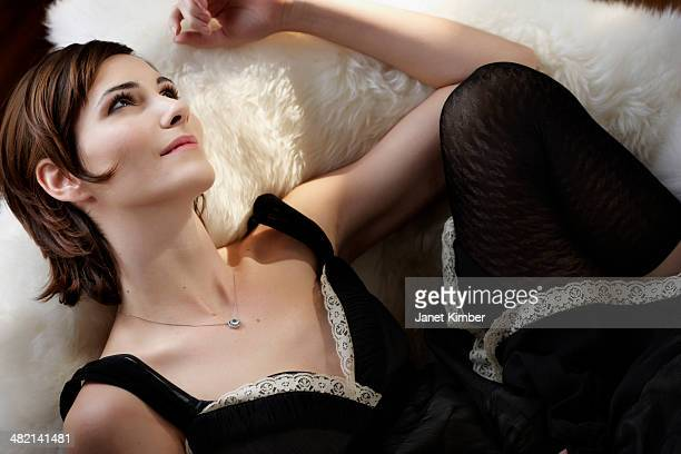 Caucasian woman laying on shag rug