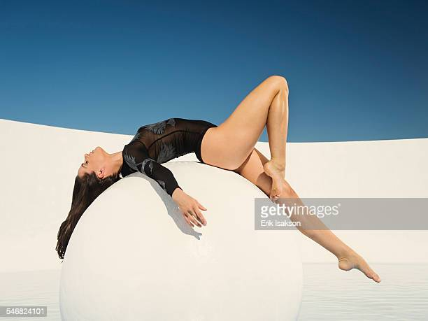 Caucasian woman laying on sphere