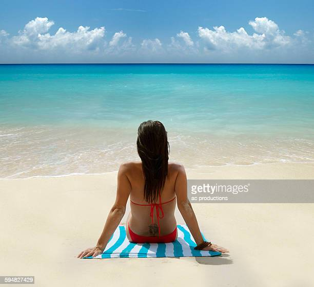 Caucasian woman laying on tropical beach