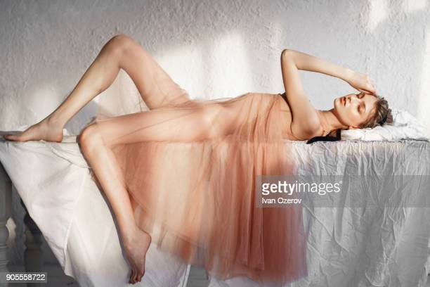 caucasian woman laying on white sheet - dressed undressed women photos et images de collection
