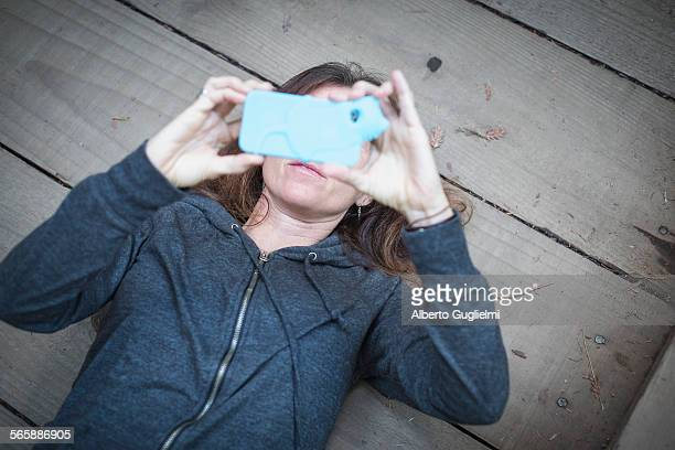 Caucasian woman laying on wooden deck taking cell phone selfie