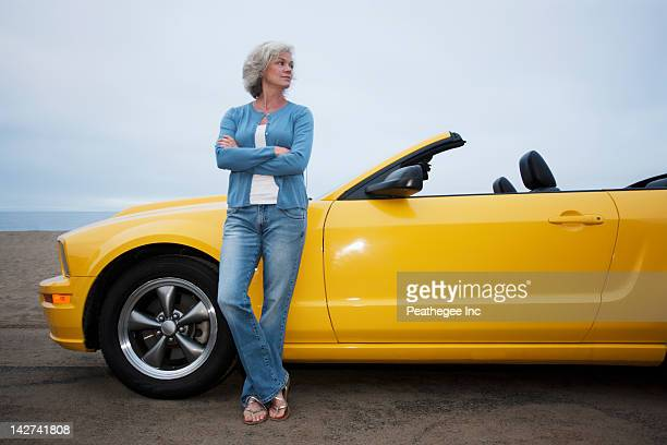 Caucasian woman leaning on convertible