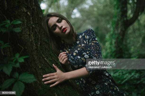 caucasian woman leaning on tree trunk - tree hugging stock pictures, royalty-free photos & images