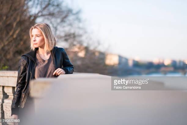 caucasian woman leaning on wall near river - endast en ung kvinna bildbanksfoton och bilder