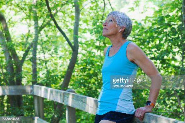 Caucasian woman leaning on wooden fence looking up