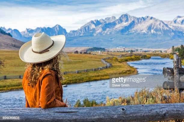 caucasian woman leaning on wooden fence near mountain river - cowgirl hairstyles stock photos and pictures