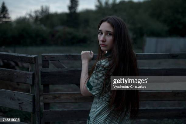 Caucasian woman leaning on wooden gate