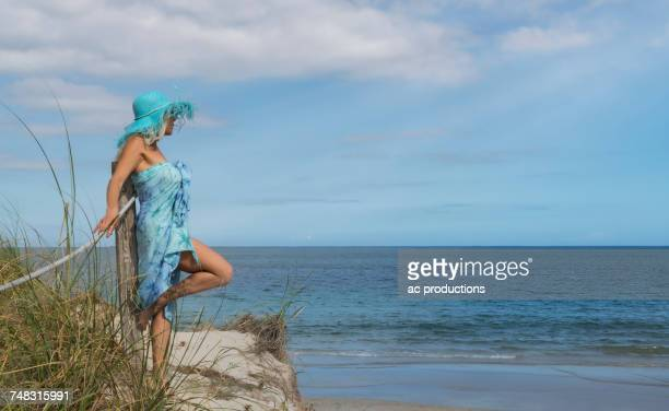 Caucasian woman leaning on wooden post at beach