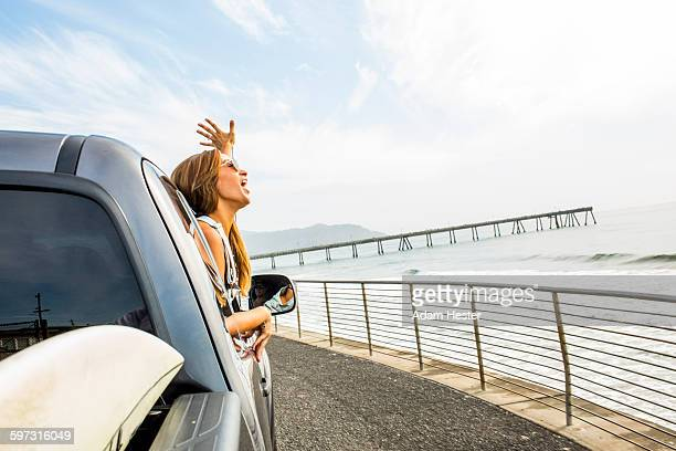 Caucasian woman leaning out car window at beach
