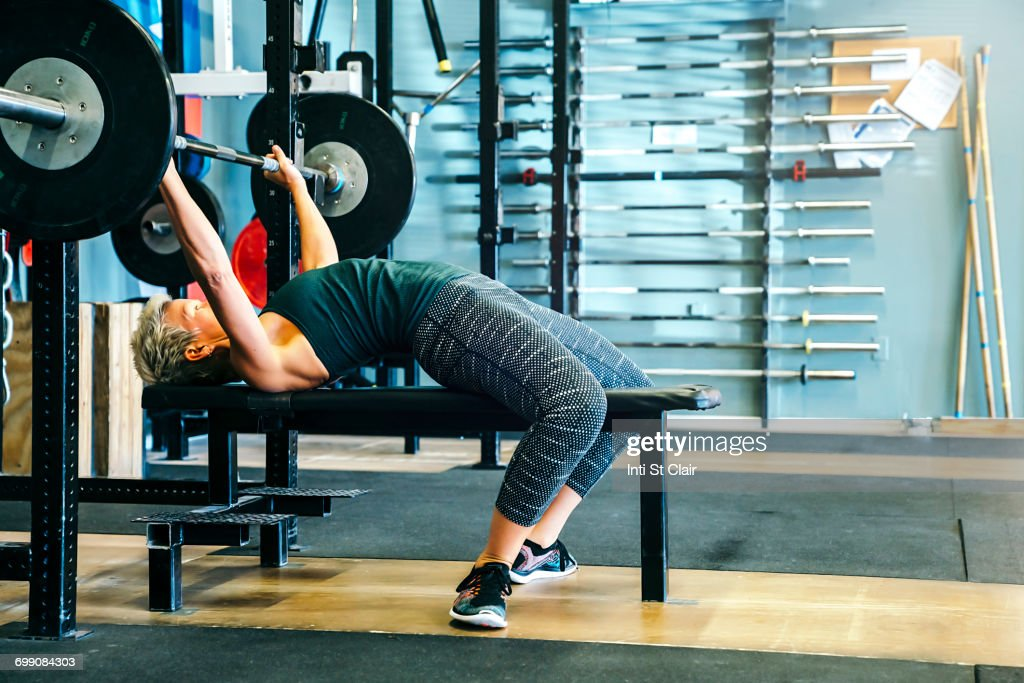Caucasian woman lifting barbell on bench in gymnasium : ストックフォト
