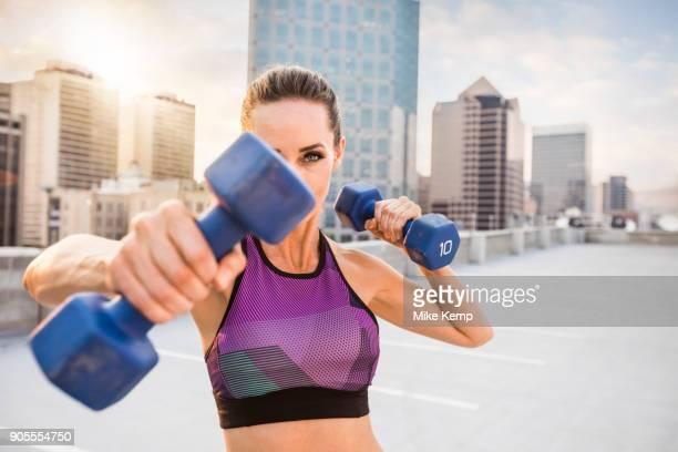 Caucasian woman lifting dumbbells on urban rooftop