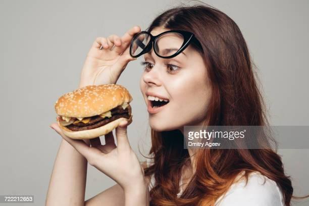 Caucasian woman lifting eyeglasses looking at cheeseburger