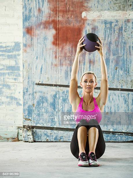 Caucasian woman lifting weights in warehouse