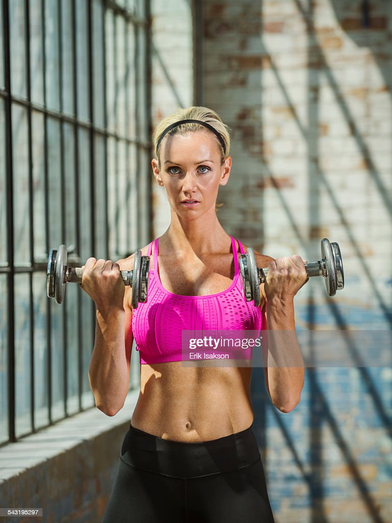 Caucasian woman lifting weights in warehouse : Stock Photo