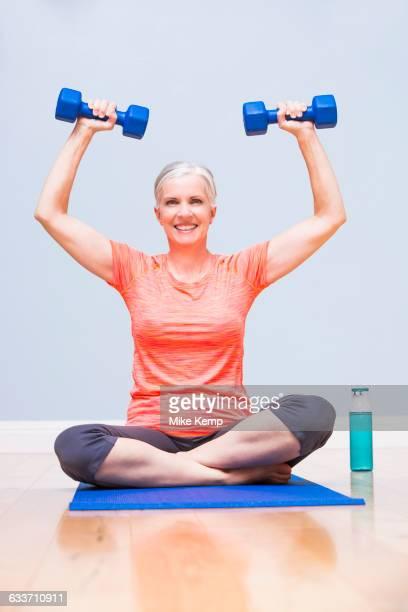 Caucasian woman lifting weights on yoga mat