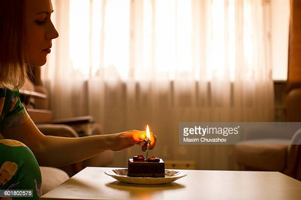 Caucasian woman lighting birthday candle on cupcake