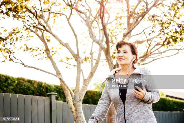 Caucasian woman listening to earbuds outdoors