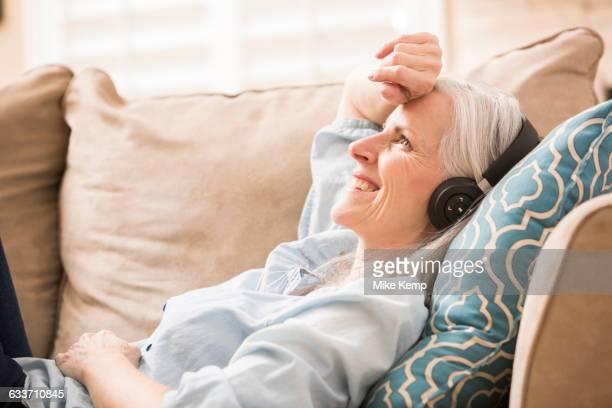 Caucasian woman listening to headphones on sofa