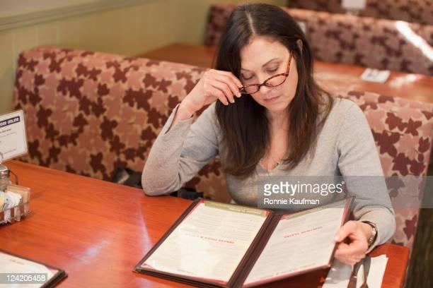Caucasian woman looking at menu in restaurant