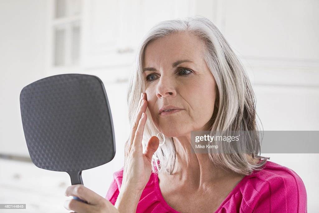 Caucasian woman looking at skin in mirror : Stock Photo