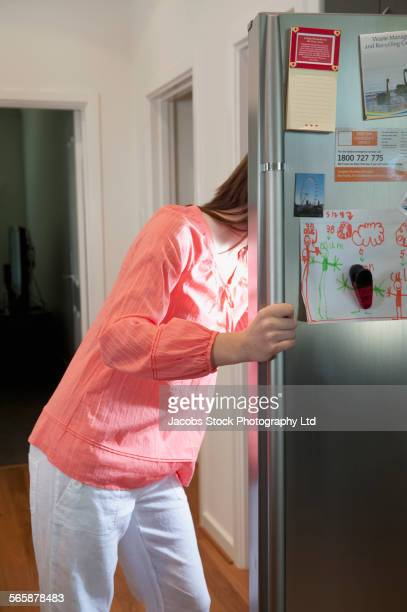 Caucasian woman looking in refrigerator