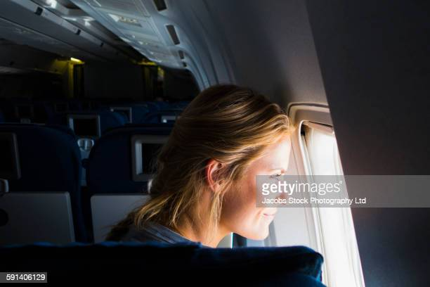 Caucasian woman looking out airplane window