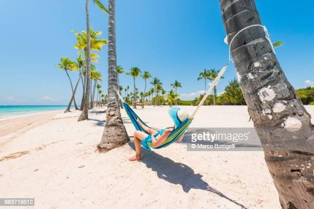 caucasian woman lying on hammock on a tropical beach. - paisajes de republica dominicana fotografías e imágenes de stock