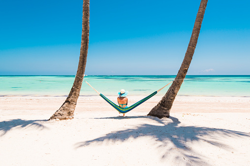 Caucasian woman lying on hammock on a tropical beach. - gettyimageskorea