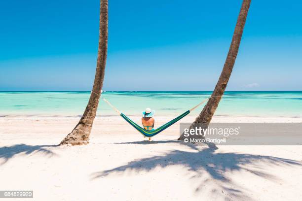 caucasian woman lying on hammock on a tropical beach. - vacances à la mer photos et images de collection