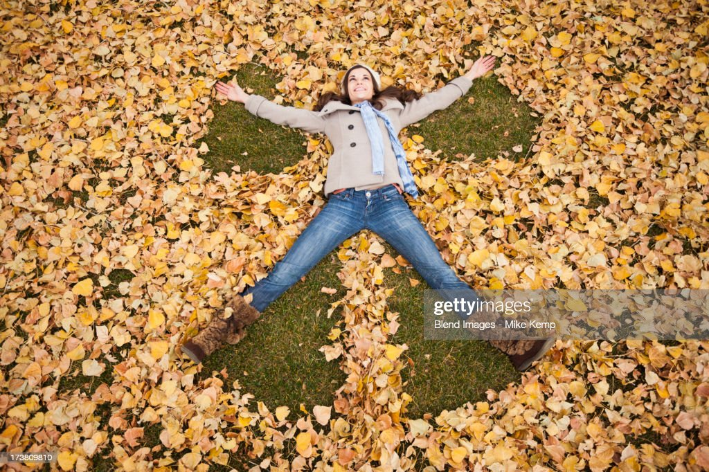 Caucasian woman making angel in autumn leaves : Stock Photo