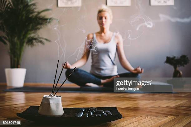 caucasian woman meditating in yoga studio - incense stock photos and pictures