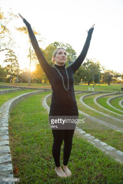 Caucasian woman meditating on grass in park