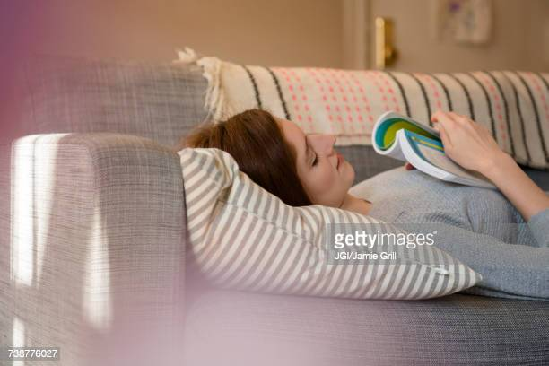 caucasian woman napping on sofa holding book - nap stock photos and pictures