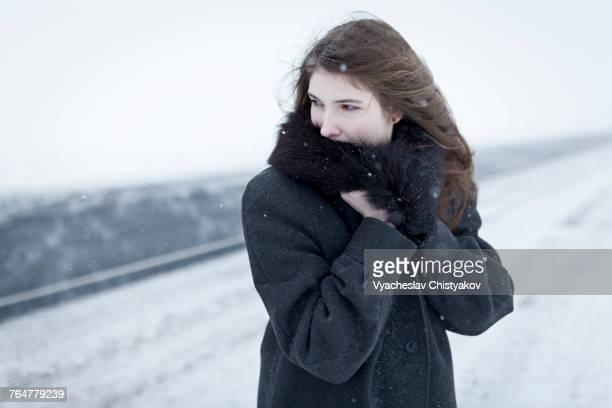 Caucasian woman nestling in fur collar outdoors in winter